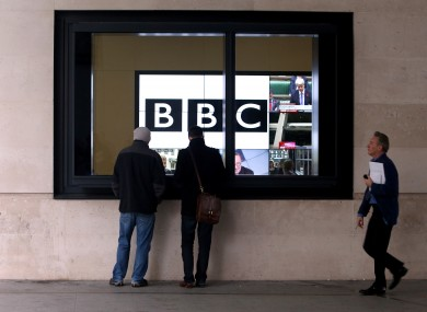 Staff walk past television screens at the BBC's Headquarters, New Broadcasting House, in central London.