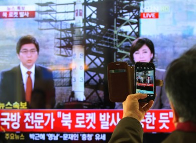A South Korean man uses his phone to take a photo of a tv reporting news about North Korea's rocket launch today
