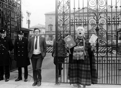 Opposition chief whip Bertie Ahern takes a breather from Dáil debates on the right-to-life referendum, as pro-life activist Margaret Mary Dunne campaigns outside.