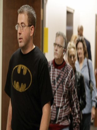 A man wears a Batman shirt as he arrives for court with other victims.