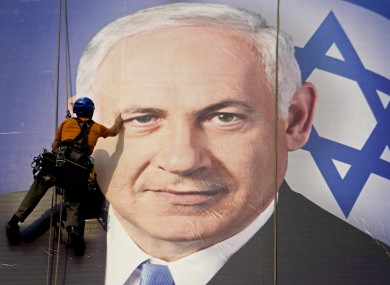 A worker hangs a huge poster with an image of Israel's Prime Minister Benjamin Netanyahu overlooking the Ayalon freeway in Tel Aviv