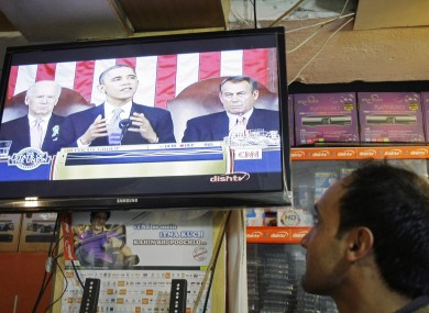An Afghan man listens to a television news report on U.S. President Barack Obama's State of the Union in Kabul