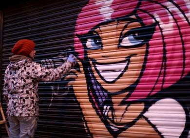 An artist working with Evolve Urban Art at John Gunn's Camera Shop on Camden St