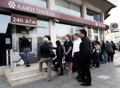 People queue at an ATM outside a closed Laiki Bank branch in Nicosia on Thursday