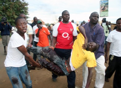 A protester is helped by others after he was shot by police in Kondele, Kisumu, Saturday, March 30, 2013 after Supreme Court declared President elect Uhuru Kenyatta as the fourth president of the Republic of Kenya.