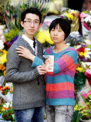 Meijiao Yu and her husband Xiao Shao hold a picture of their daughter Jiayi.