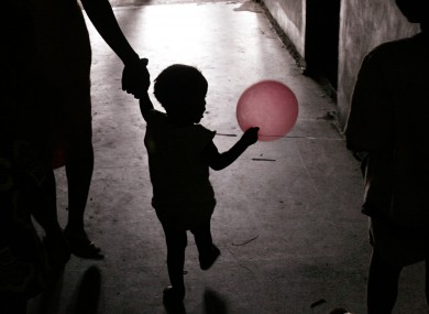 A little girl plays with a pink balloon in the hallway of an abandoned government building that is home to hundreds of squatters, in Monrovia, Liberia