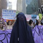 Women chant slogans, one wearing an burka, as they march in a