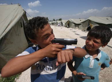 Jamal, an 11-year old Syrian refugee, left, points his toy gun as he plays with his friend, at a temporary refugee camp in the eastern Lebanese town of Marj near the border with Syria.