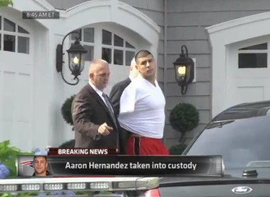 Hernandez is led away by police.