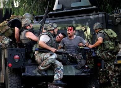 Lebanese army soldiers help injured soldiers after clashes between followers of a radical Sunni cleric Sheik Ahmad al-Assir and Shiite gunmen, in the southern port city of Sidon, Lebanon today.