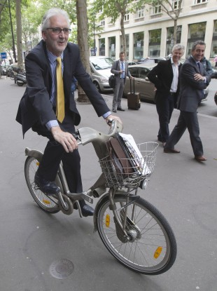 British Cycling President, Brian Cookson, rides a bike as he poses for photographers after a press conference in Paris earlier.