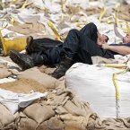 Helpers take a break on a wall of sandbags in a flooded area by river Elbe in Magdeburg, central Germany. (AP Photo/Jens Meyer)