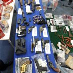 Range of seized weapons and ammunition on display.<span class=