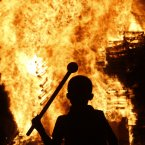 A boy watches a bonfire in the Protestant Sandy Row area of Belfast, Northern Ireland. Hundreds of fires were set alight Thursday as loyalists celebrate The Twelfth, the holiday remembering the defeat of the Catholic King James, by the Protestant William of Orange in 1690. (AP Photo/Peter Morrison)