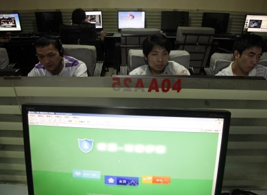 In this photo taken Wednesday, July 14, 2010, Chinese men use computers at an Internet cafe in Beijing.