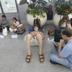 Bob Merberg sits with son Oren, 19, and daughter Maya, 16, after their flight to Rochester, New York was canceled after Asiana Flight 214 crashed at San Francisco International Airport in San Francisco. (AP Photo/Jeff Chiu)