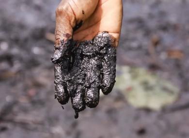Pastor Christian Lekoya Kpandei's hand covered in oily mud, Bodo Creek, Nigeria, 2011.