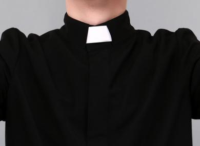 Priest on grey background