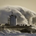 People watch and photograph enormous waves as they break on Porthcawl harbour.<span class=