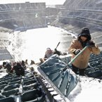 Henry Claudio, from Delaware, shovels snow up in the north end zone seating area at Lincoln Field in Philadelphia<span class=