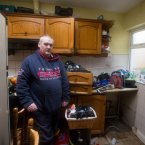 Brian O'Brien shows the damage done by floods inside his house. <span class=