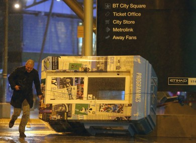 A programme stand blown over amidst the heavy wind and rain outside the Etihad Stadium.