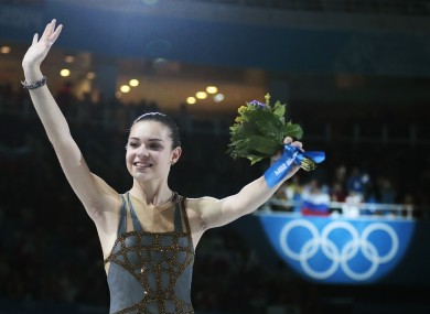Adelina Sotnikova of Russia celebrates after placing first during the flower ceremony for the women's free skate figure skating final at the Iceberg Skating Palace.
