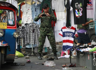 A soldier photographs the scene of an explosion littered with blood and small pairs of shoes at a main protest site in Bangkok.