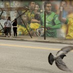A mural of Brazilian soccer player Neymar, right, and others cover a wall by a bus stop in Sao Paulo, Brazil. The mural was painted by Brazilian street artist Rodolfo Turini ahead of the World Cup soccer tournament that starts in June.<span class=
