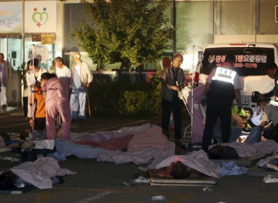Rescued patients are placed on the ground outside the hospital.