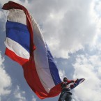 An anti-government protester waves a Thai national flag during a rally in Bangkok, Thailand. <span class=