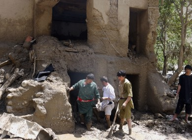 Afghans look for their belongings in their house damaged after flooding in the northeastern Baghlan province, north of Kabul.