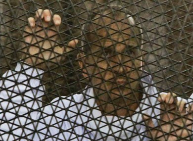 In this file photo taken Wednesday, March 5, 2014, Al Jazeera journalist Peter Greste stands inside the defendants' cage in a courtroom during a trial on terror charges, along with several other defendants, in Cairo Egypt.