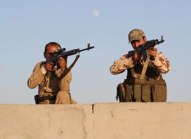 Kurdish Peshmerga fighters stand guard during airstrikes targeting Islamic State militants.