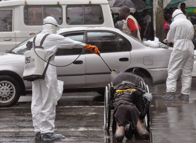Health workers spray the body of an amputee suspected of dying from Ebola in Liberia