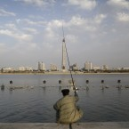 A man sits facing the Tower of the Juche Idea as he fishes off the Taedong River bank in Pyongyang, North Korea. (AP Photo/Wong Maye-E)<span class=