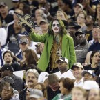 A New Orleans Saints fan dressed as the comic book character, the Joker, watches play during the second half of an NFL football game against the Dallas Cowboys.<span class=