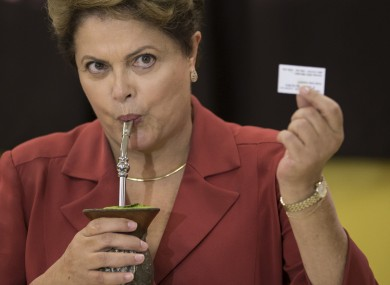 Rousseff, shows her electronic voting receipt as she drinks mate, an herbal tea, on Sunday.
