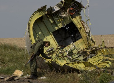 A pro-Russian rebel touches the MH17 wreckage at the crash site of Malaysia Airlines Flight 17