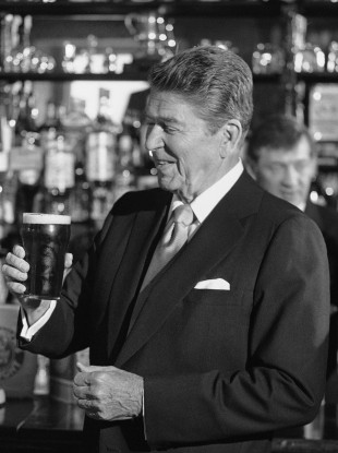 US President Ronald Reagan contemplates a pint glass of Irish stout, at the bar of O'Farrells Pub in the centre of the village of Ballyporeen in 1984.