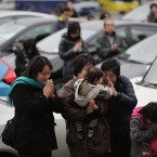 People pray next to their cars during New Year's prayer service for the traffic safety of vehicles near Tokyo.<span class=