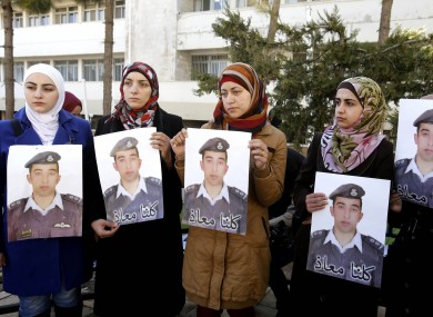 Anwar al-Tarawneh, center, the wife of the Jordanian pilot holds a poster of him, with Arabic that reads,