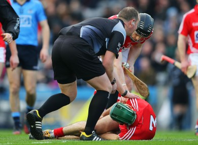 Referee Alan Kelly and Cork defender Shane O'Neill check on the injured Christopher Joyce.
