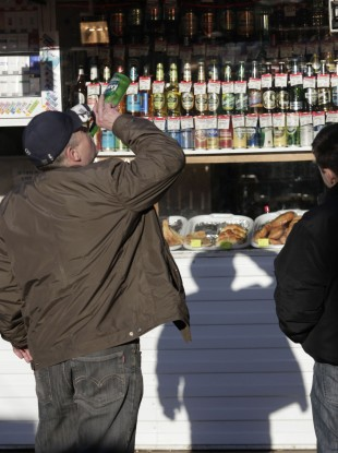 File: A Russian man drinks from a bottle standing in front of a liquor booth in a street in Moscow