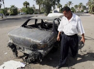 An Iraqi traffic policeman inspects a car destroyed by a Blackwater security detail in al-Nisoor Square in Baghdad in 2007.