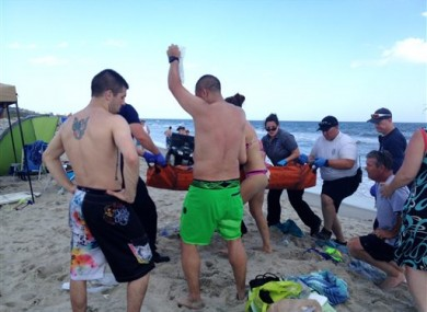 File photo of emergency responders assisting a teenager at the scene of a shark attack in Oak Island, N.C.