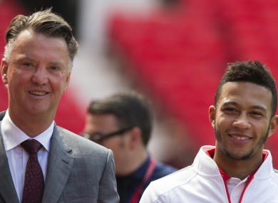Manchester United's new player Memphis Depay, right, smiles as he walks alongside manager Louis van Gaal.