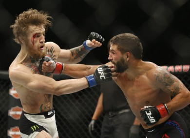 Chad Mendes, right, punches Conor McGregor during their interim featherweight title mixed martial arts bout at UFC 189.