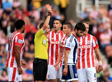 Michael Oliver (left) gives a red card to Stoke City's Ibrahim Afellay.